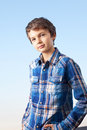 Sunny boy a teenage is making a cool pose and is smiling friendly into the camera Royalty Free Stock Images