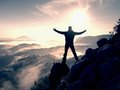 Sunny fall morning. Happy hiker with raised hands in air stand on rock Royalty Free Stock Photo