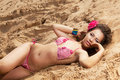 Sunny girl lying on sand with red flower Royalty Free Stock Images