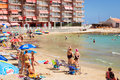 Sunny mediterranean beach tourists relax on sand people bathe torrevieja spain september warm loungers under parasols in Stock Photo