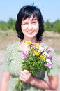 Sunny outdoors vintage portrait woman bunch field flowers one eye closed Stock Photography