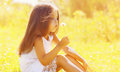 Sunny portrait of cute little girl child blowing flowers Royalty Free Stock Photo