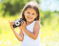 Sunny portrait of cute smiling little girl child with old camera Royalty Free Stock Photo