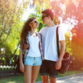 Sunny portrait of happy young couple teenagers in urban style outdoors boyfriend embracing girl the park Stock Image