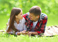 Sunny portrait of sweet young couple lying relaxing on the grass Royalty Free Stock Photo