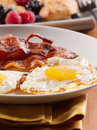Sunny side up eggs with fried bacon. Royalty Free Stock Images