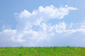 Sunny spring background clouds blue sky green grass Royalty Free Stock Photo