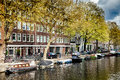Sunny spring day in Amsterdam. Canal view with boats and bicycles, Netherlands Royalty Free Stock Photo