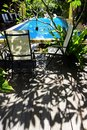 Sunny tropical pool side a photograph showing the beautiful sunlight and shadows of a plumeria tree by the of a blue swimming Stock Photos