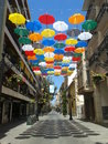Sunny umbrellas above the streets of gandia spain hang these brightly coloured to depict the start of the sales in the shops they Royalty Free Stock Photo