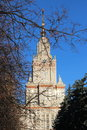 Sunny view of Moscow State University main building with reflections in windows through autumn tree branches Royalty Free Stock Photo