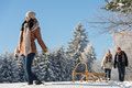 Sunny winter day woman pulling sledge women couple walking in snow Royalty Free Stock Images