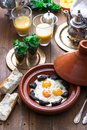 Sunnyside Eggs cooked in a Tajine dish with beef, Moroccan breakfast with juice and mint tea Royalty Free Stock Photo