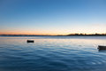 Sunrise across bay with small dinghy blue tones with orange arou Royalty Free Stock Photo
