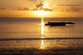 Sunrise with an african boat dhow at the beach at the foreground zanzibar tanzania Stock Image