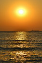 Sunrise on the beach with waves, a boat on the horizon and two birds flying Royalty Free Stock Photo