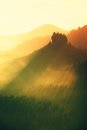 Sunrise in a beautiful mountain of Czech-Saxony Switzerland. Sharp hills increased from foggy background, the fog is orange due to Royalty Free Stock Photo