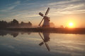 Sunrise behind dutch windmill misty by river holland Stock Photo