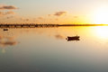 Sunrise and calmness over tauranga harbour water ripples bird on boat historic rail bridge on horizon Stock Photo