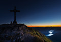 Sunrise landscape with glowing horizon and summit cross Stock Photos
