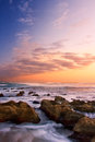 Sunrise landscape of ocean with waves clouds and rocks on beach Stock Photos