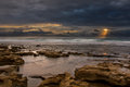 Sunrise landscape of ocean with waves clouds and rocks on beach Stock Image