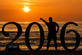 Sunrise man silhouette pointing out sun of young forming new year the at dawn at sea Stock Photos