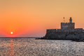 Sunrise in mandraki harbour rhodes greece agios nikolaos fortress on the of Stock Photography