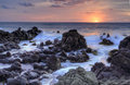 Sunrise and minamurra volcanic rocks at low tide over the rugged craggy ocean flows Royalty Free Stock Image