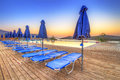 Sunrise at mirabello bay in greece with empty deck chairs Stock Image