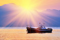 Sunrise over the bay old fishing boat in at against mountains Royalty Free Stock Photo