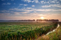 Sunrise over green pastoral summer dutch with canal Royalty Free Stock Photo
