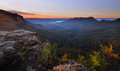 Sunrise over jamison valley mt solitary from narrowneck overlooking the a light fog and mist as first rays of sunlight strike the Stock Image