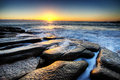 Sunrise over the ocean overlooking horizon on a rocky shore in magical hour of Royalty Free Stock Photography