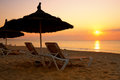 Sunrise over the parasol on the beach tunisia in Stock Photo