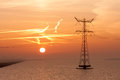 Sunrise over the sea with an electricty pylon Royalty Free Stock Photo