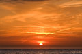 Sunrise at sea with aerial wakes image of or sunset the half of the sun behind clouds and in the sky Stock Images