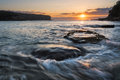 Sunrise seascape with rushing water and rising sun and backlit waves Royalty Free Stock Images