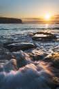 Sunrise seascape with rushing water and rising sun and backlit waves Stock Photo