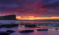 Sunrise skies over avalon on sydney s northern beaches the sunise of rich red and yellow hues with views to the headland a cargo Stock Photo