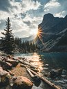 Sunrise with turquoise waters of the Moraine lake with sin lit rocky mountains in Banff National Park of Canada in Royalty Free Stock Photo