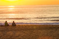 Sunrise two asian males beach seated at the in durban south africa with sitting on the near the water shoreline photo image from Royalty Free Stock Image