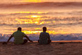 Sunrise two asian males beach seated for a new day at the in durban south africa with sitting on the near the water shoreline Royalty Free Stock Photography