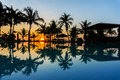 Sunrise via swimming pool and silhouette coconut tree Stock Images