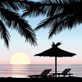 Sunrise view at resort seaside holiday background relaxing landscape two chaise longue and parasol on beach with palm tree Royalty Free Stock Images