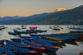 Sunrise with wooden boats on Phewa lake, Pokhara, Nepal.