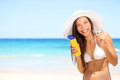 Sunscreen beach woman in bikini applying sun block solar cream for uv protection girl smiling to camera wearing white hat Stock Images