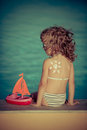 Sunscreen lotion drawing sun on children back summer vacation concept Royalty Free Stock Image
