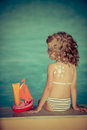 Sunscreen lotion drawing sun on childrens back summer vacation concept Stock Photos