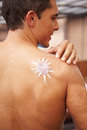 Sunscreen in sun shape on male back Royalty Free Stock Images